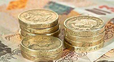 A pile of British pound coins on ten pound notes