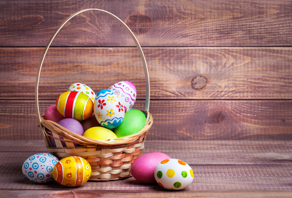 Easter eggs in the basket of wooden boards